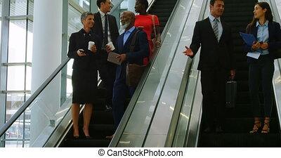 Business people talking on escalator 4k - Business people...