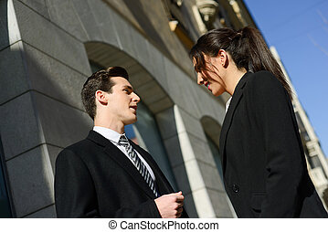 Business people talking outside of company building. Couple work