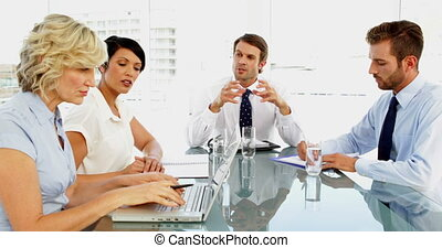 Business people talking with their boss during meeting in...