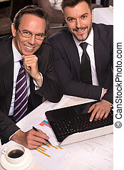 Business people. Top view of two business people in formalwear smiling at camera while working on laptop