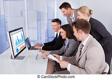 Business People Using Computer And Laptop In Office