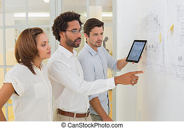 Business people using digital tablet in meeting at office -...
