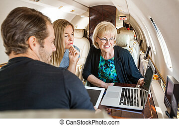 Business People Using Laptop In Private Jet