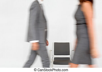 Business people walking by chair set in hallway