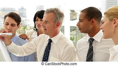 Business people watching man write