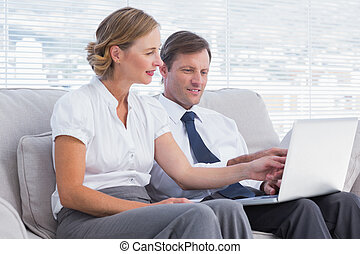 Business people watching something on laptop