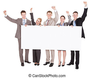 Business People With Arms Raised Holding Blank Billboard