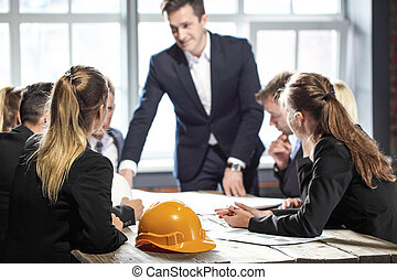Business people with construction blueprint