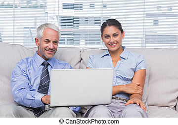 Business people with laptop smiling at camera