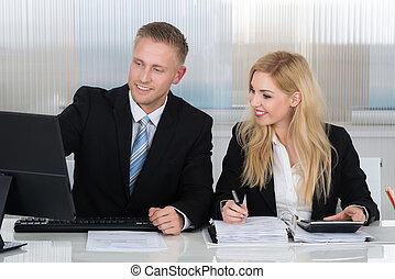 Business People With Paperwork Discussing Over Computer At Desk