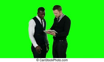 Business people working on a tablet. Green screen