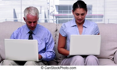 Business people working on laptops side by side on the couch