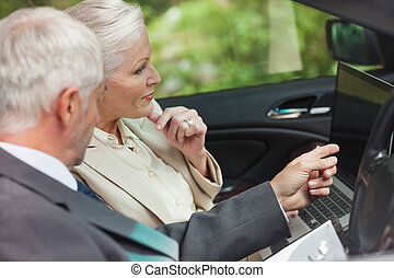 Business people working together in classy cabriolet on a ...