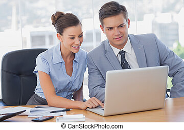 Business people working together on laptop and smiling in...