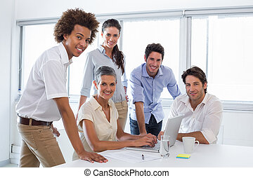 Business people working with laptop and smiling at camera