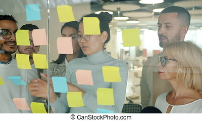 Business people working with sticky notes in office using ...