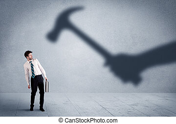 Business person afraid of a shadow hand holding hammer concept