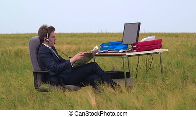 Business person reading newspaper at office desk in a green...