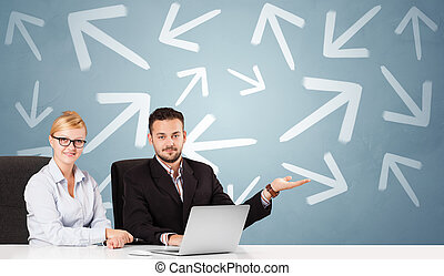Business person sitting at desk with direction concept