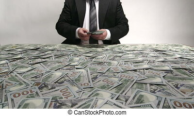Business person sorting and counting a lot of hundred dollar bills at desk