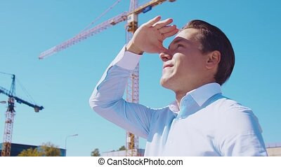 Business person standing in front of construction site. ...
