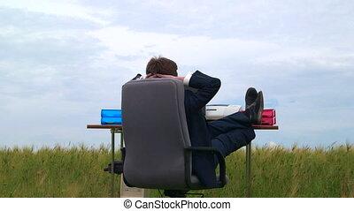 Business person taking break at office desk in a green field