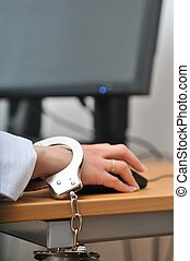 Business person tied with handcuffs to workplace