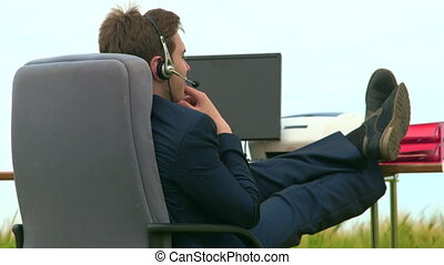 Business person wearing headset during VoIP conversation at...
