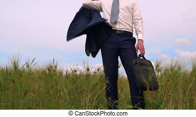 Business person with bag standing in a green field