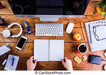 Business person working at office desk holding a notebook