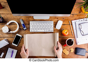 Business person working at office desk holding paper roll