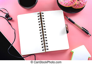 Business photo. A tablet with headphones. An open notepad . Coffee and donuts.
