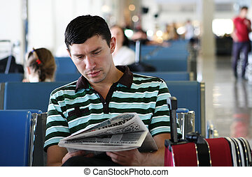 Business - Man reading newspaper at the airport in the...