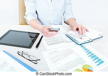Successful businesswoman sitting at desk in casual clothes and planning her working day in the office