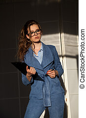business portrait of a woman in a business suit with a folder for papers