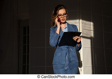 business portrait of a woman in a business suit with a Smartphone and a folder for papers