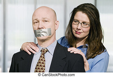 Portrait of Business team - the man is being muzzled with duct tape