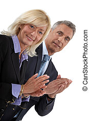 Business professionals clapping their hands