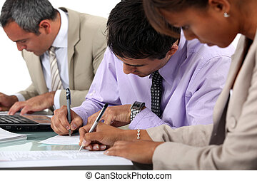 Business professionals filling in paperwork