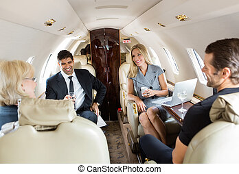 Business Professionals Having Drinks On Private Jet