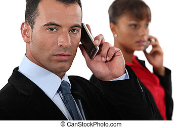 Business professionals talking on their mobile phones