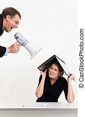 Portrait of confident boss shouting at woman under laptop