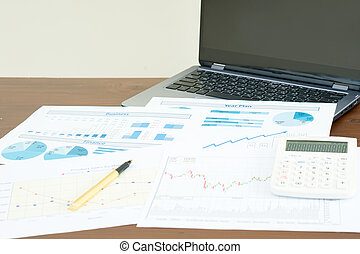 Business report and laptop on desk