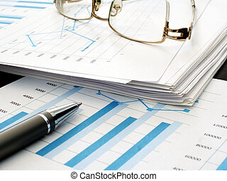 Business report with financial charts. Stack of papers in the office.