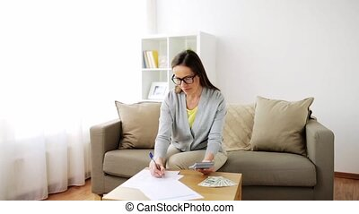 woman with money, papers and calculator at home