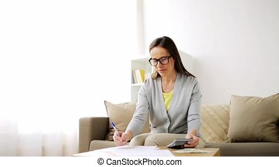 woman with money, papers and calculator at home - business,...