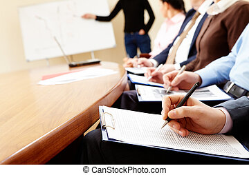 Close-up of businesspeople hands holding pens and papers near table at business seminar