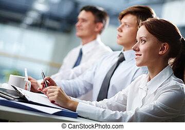 Business seminar - Three business people sitting at seminar,...