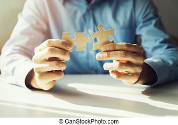 business solutions - businessman connecting jigsaw puzzle
