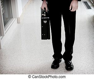 business stance - Business man standing in the hallway with...
